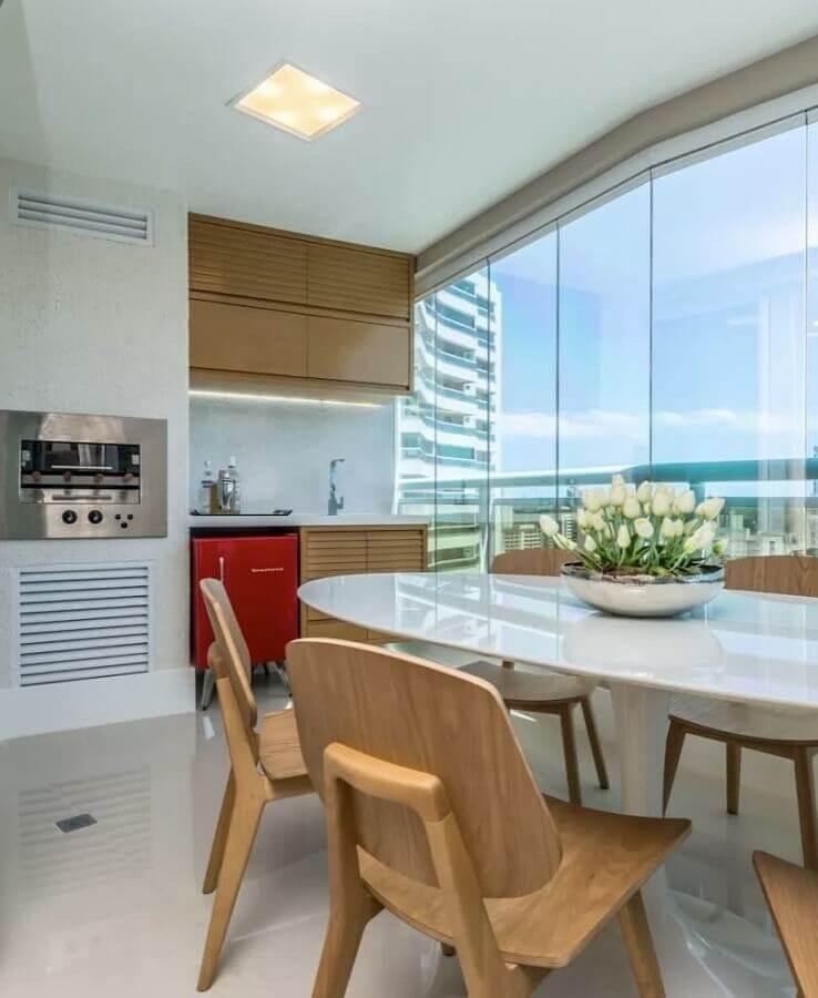 Apartamento com varanda gourmet decorada com cadeiras e armários de madeira Foto Homify