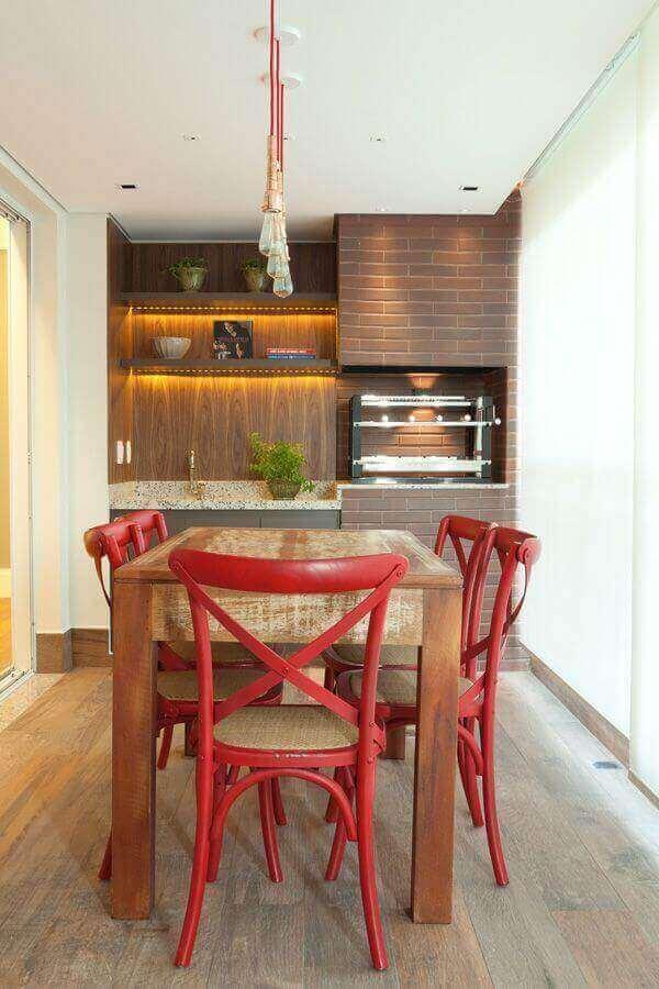 Apartamento com varanda gourmet decorado com cadeira vermelha para mesa de madeira rústica Foto Liliana Zenaro