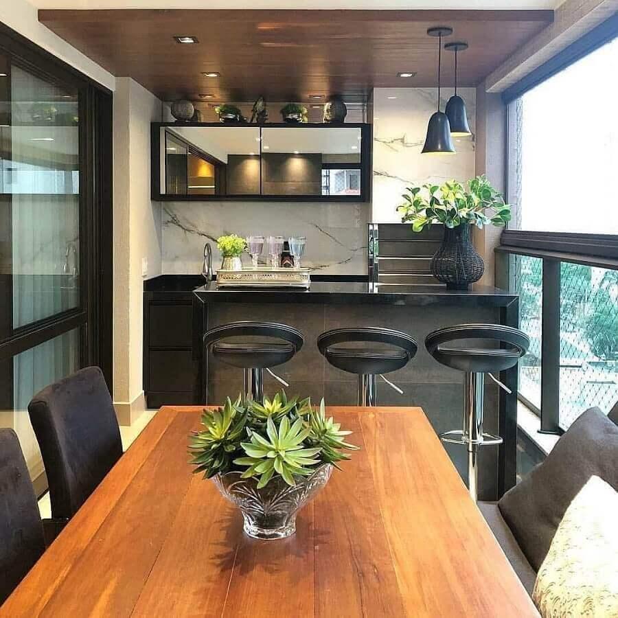 Apartamento com varanda gourmet e churrasqueira decorada com mesa de madeira e banqueta preta Foto Jeito de Casa