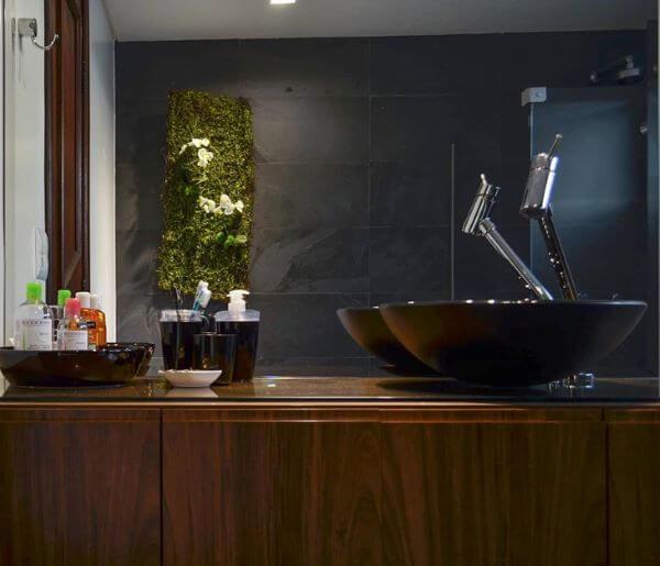 Banheiro com ardósia preta na parede e móveis de madeira
