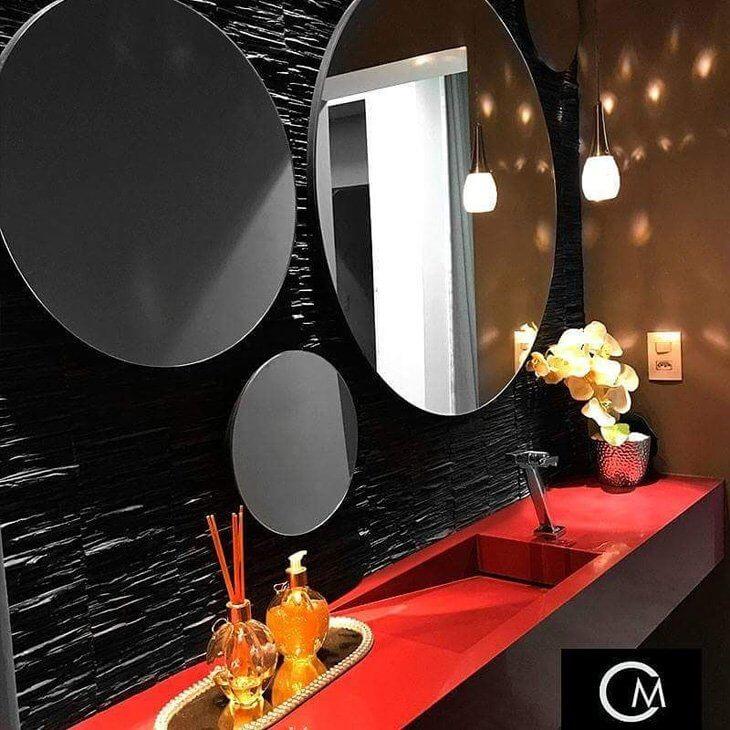 Banheiro com parede de filetes de ardósia preta, espelhos redondos e bancada vermelha