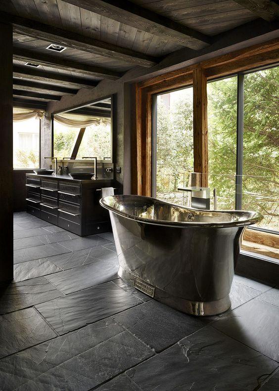Banheiro com piso de ardósia preta e banheira de ferro