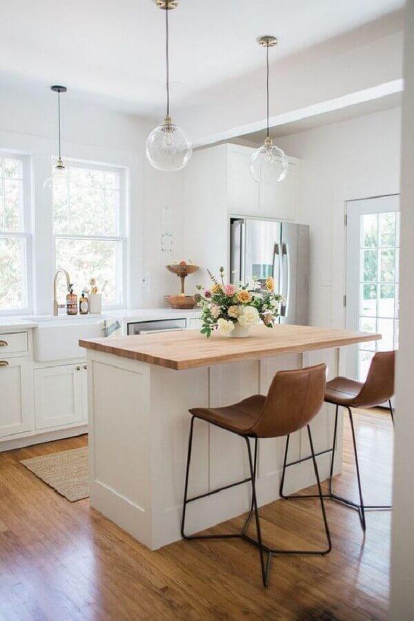 Banquetas estofadas para ilha de cozinha branca decorada com luminária de vidro Foto Arquitetas Express