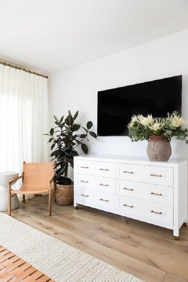 Cômoda branca grande para quarto amplo decorado com poltrona de madeira e vaso de planta no chão Foto Apartment Therapy