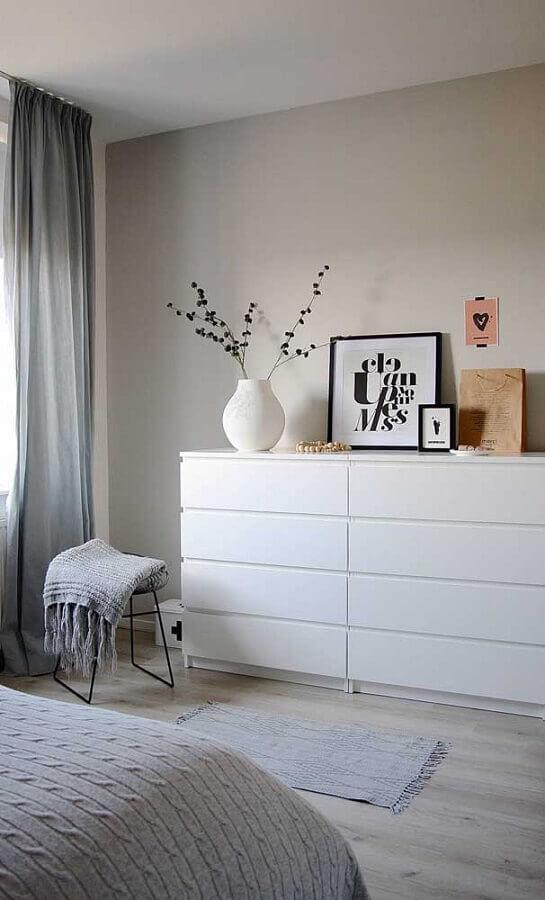 Cômoda branca para quarto de casal minimalista decorado com cortina cinza e piso de madeira clara Foto Apartment Therapy