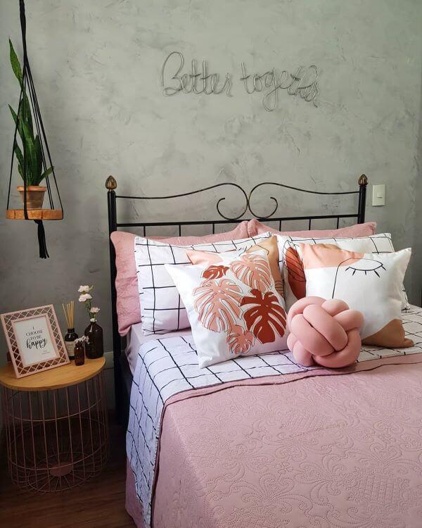 Cama decorada com almofadas grandes em tons de rosa e branco