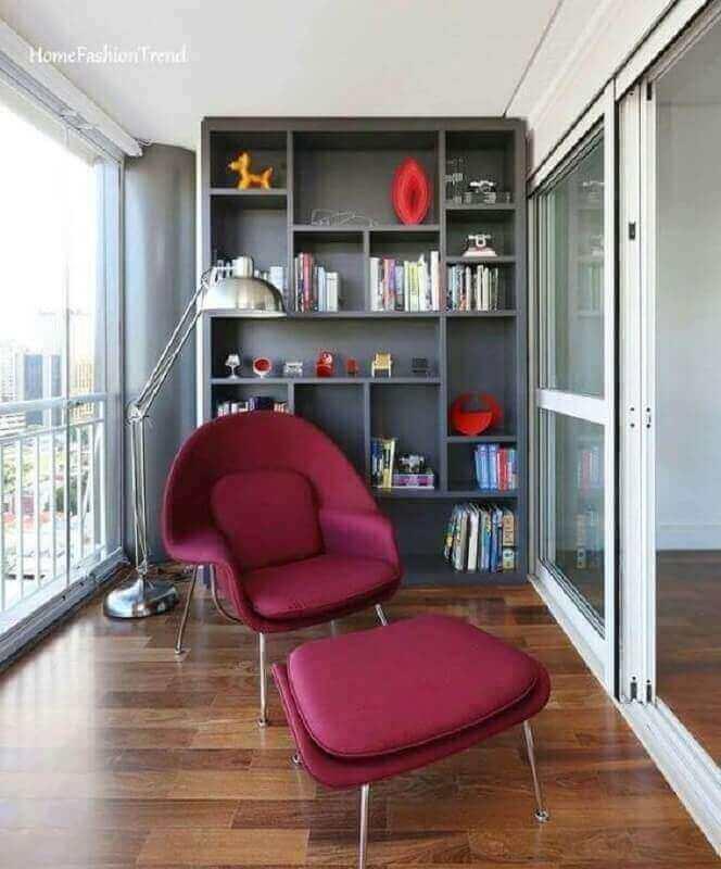 Cantinho de leitura na varanda decorada com estante cinza e poltrona confortável com puff Foto Home Fashion Trend