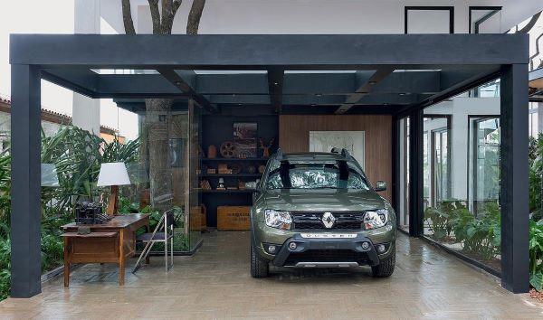 Casa com garagem de vidro e pergolado de ferro