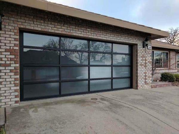 Casa com portão de vidro jateado na garagem
