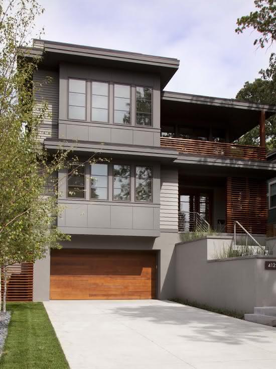 Casa grande com cerâmica para garagem cinza e portão de madeira