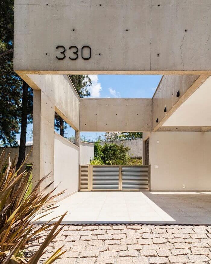 Casa moderna com cerâmica para garagem em bege e piso de pedra