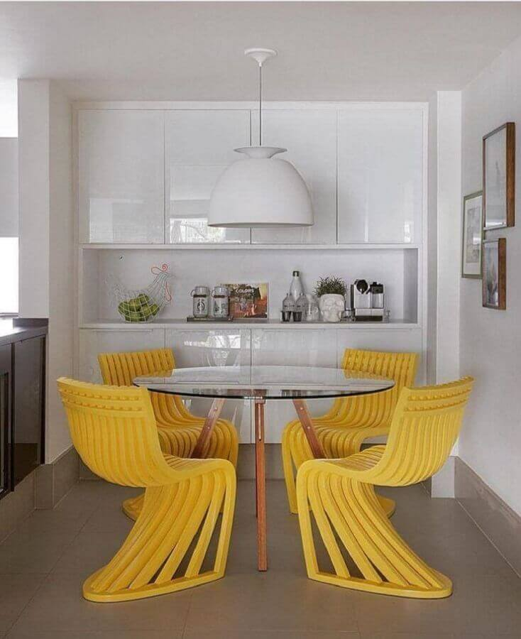 Cores para sala de jantar pequena decorada com cadeiras amarelas para mesa de vidro redonda Foto Yamagata Arquitetura