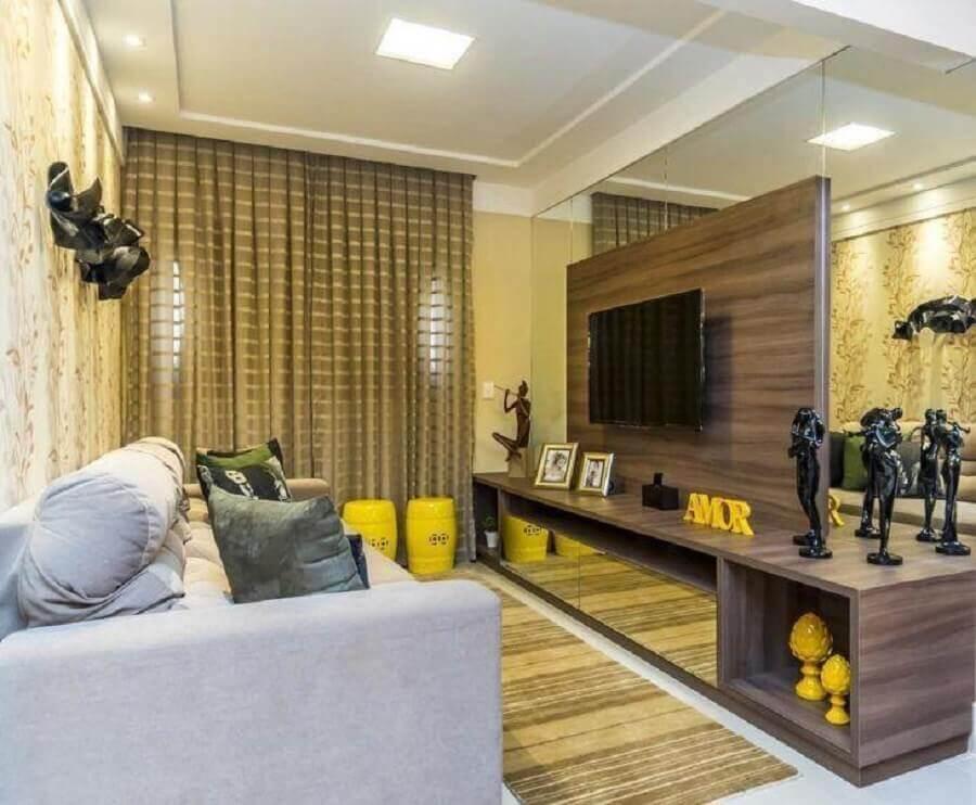 Cores para sala pequena decorada com parede espelhada e rack de madeira com painel para TV Foto Renove Projetos