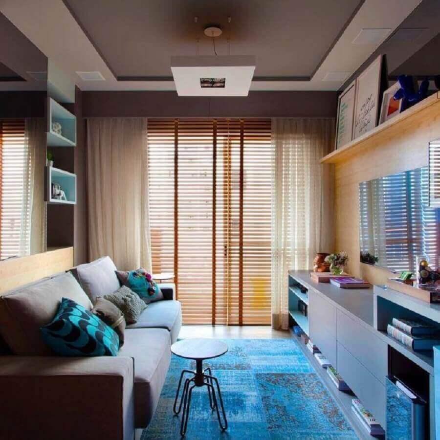 Cores para sala pequena decorada com tapete azul e persiana de madeira Foto Juliana Pippi