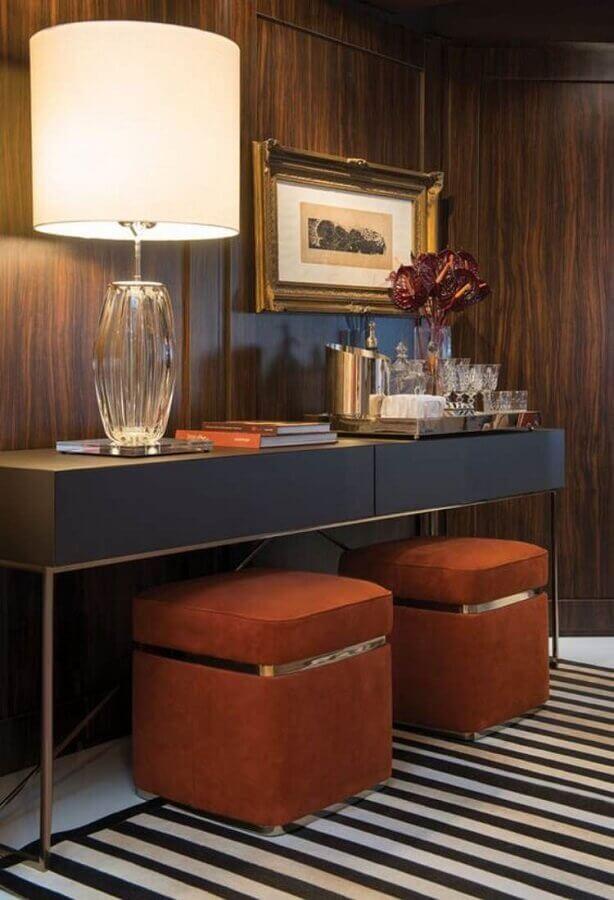 Corredor decorado com parede de madeira e puff banqueta quadrado embaixo de aparador Foto Habitare
