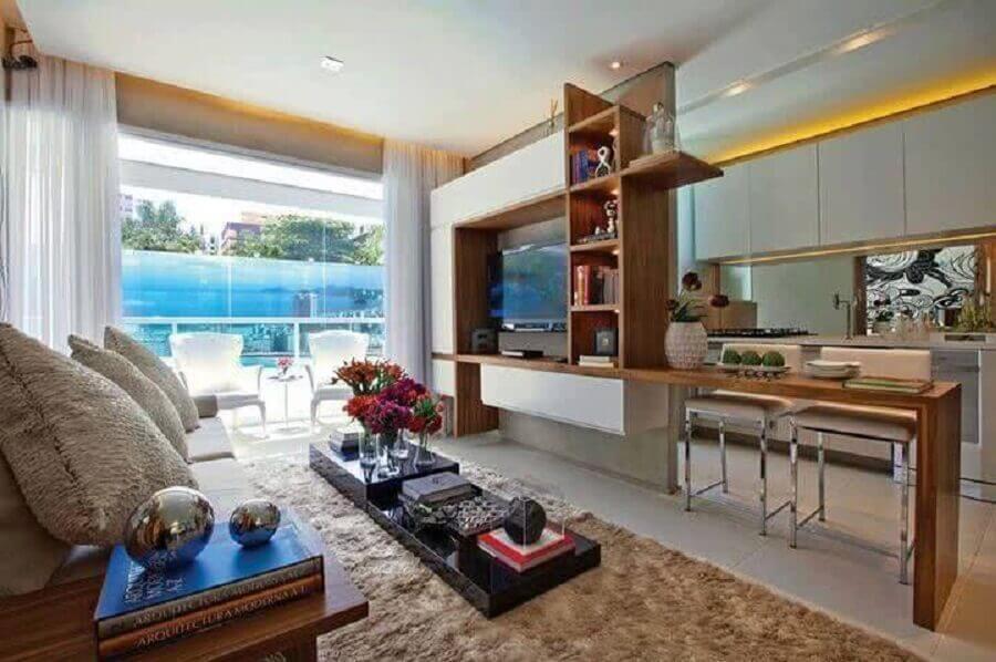Cozinha aberta com sala de TV decorada com tapete bege felpudo Foto BOQ News
