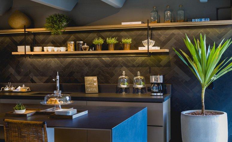 Cozinha com revestimento de ardosia preta e prateleiras de madeira para organizar o ambiente