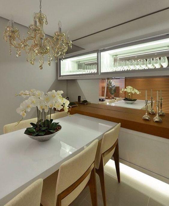Cristaleira pequena de parede na sala com mesa de jantar retangular branca
