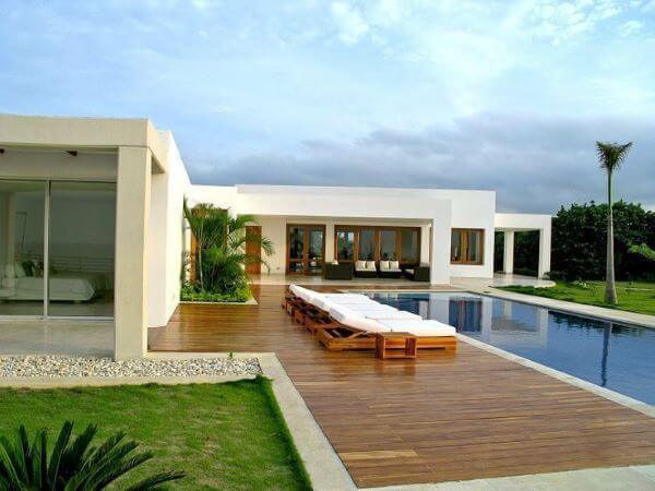 Deck de madeira para piscinas modernas em frente a casa