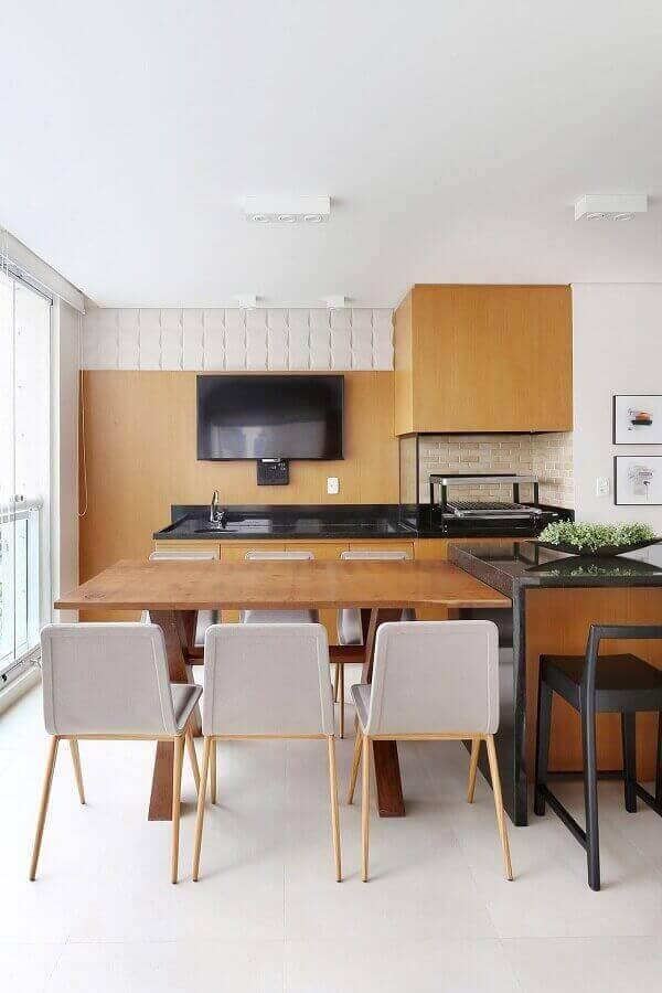 Decoração clean com revestimento de madeira para apartamento com varanda gourmet e churrasqueira de vidro Foto Renata Popolo