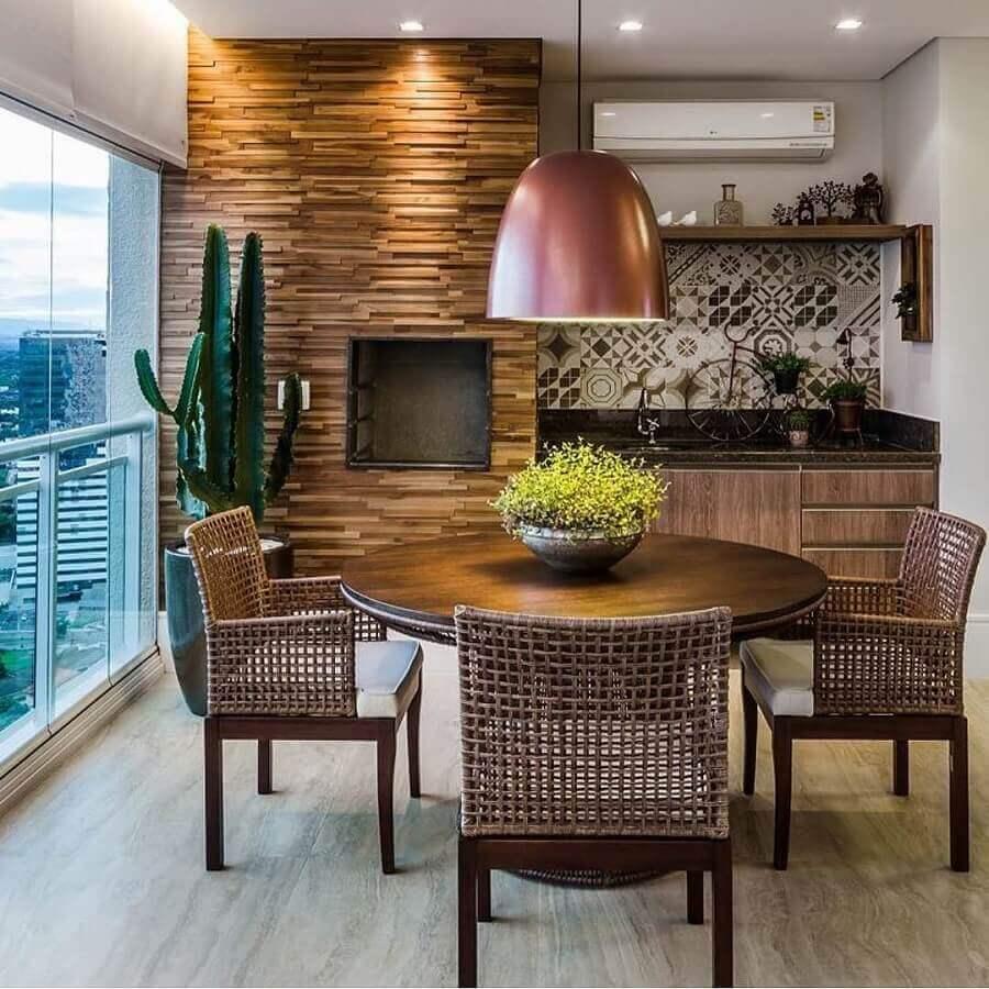 Decoração com lustre para área gourmet com revestimento de madeira e mesa redonda Foto Pinterest