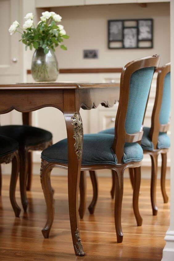 Decoração com móveis vintage e mesa provençal com cadeira azul de madeira