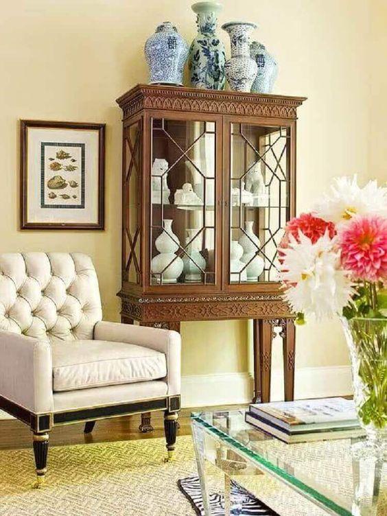 Decoração com móveis vintage para sala de estar com cristaleira e poltrona