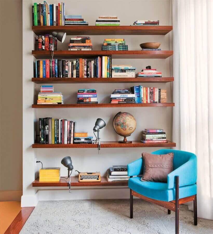 Decoração com prateleiras de madeira para livros e poltrona confortável para leitura Foto Jeito de Casa