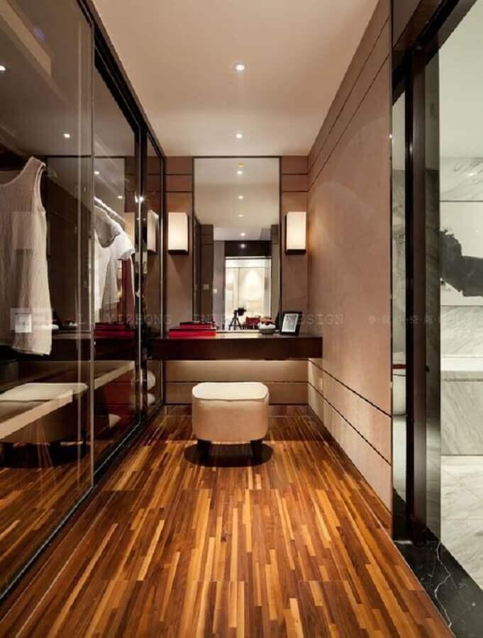 Decoração de closet com piso de madeira e banqueta puff pequeno Foto Casa Très Chic