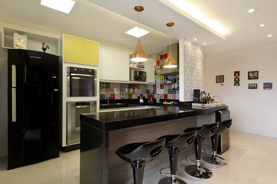 Decoração de cozinha aberta com revestimento colorido e banquetas pretas Foto Juliana Conforto