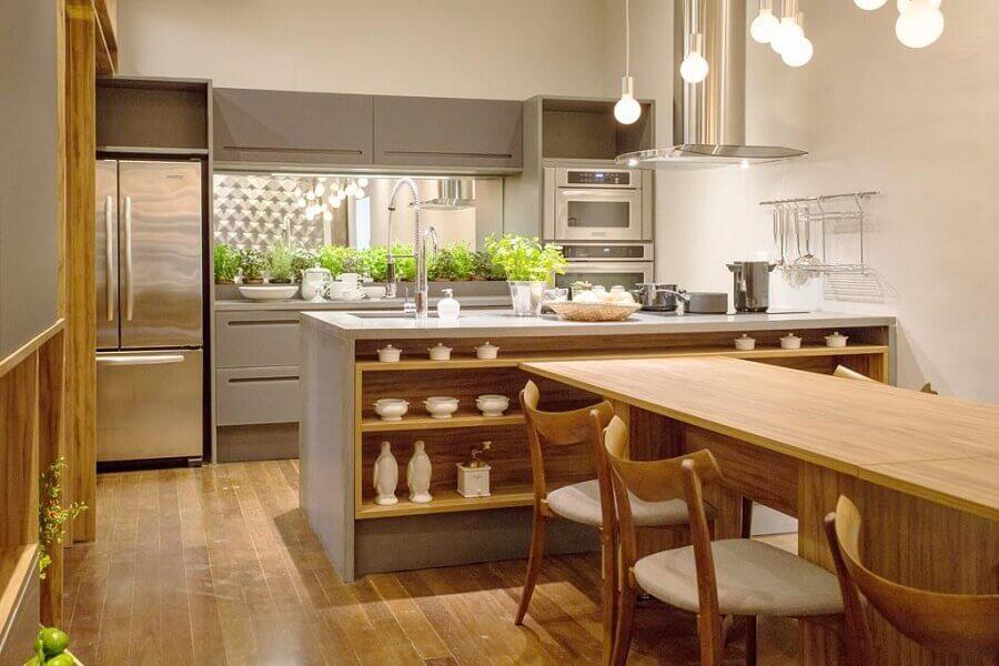 Decoração de cozinha aberta planejada com bancada de concreto com mesa de madeira integrada Foto Mary Oglouyan