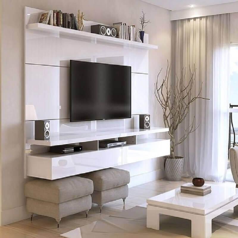 Decoração de sala de TV com rack suspenso e puff banqueta quadrado Foto Overstock