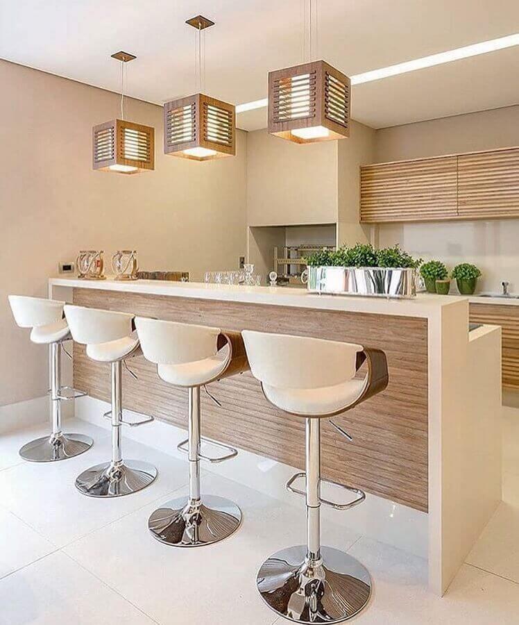 Decoração em cores claras com banqueta alta e lustre pendente para área gourmet Foto Jeito de Casa