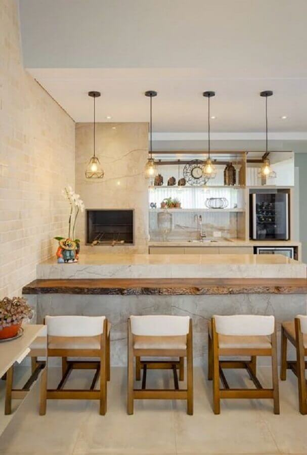 Decoração em cores neutras com lustre pendente para área gourmet com bancada de madeira rústica Foto Architrends