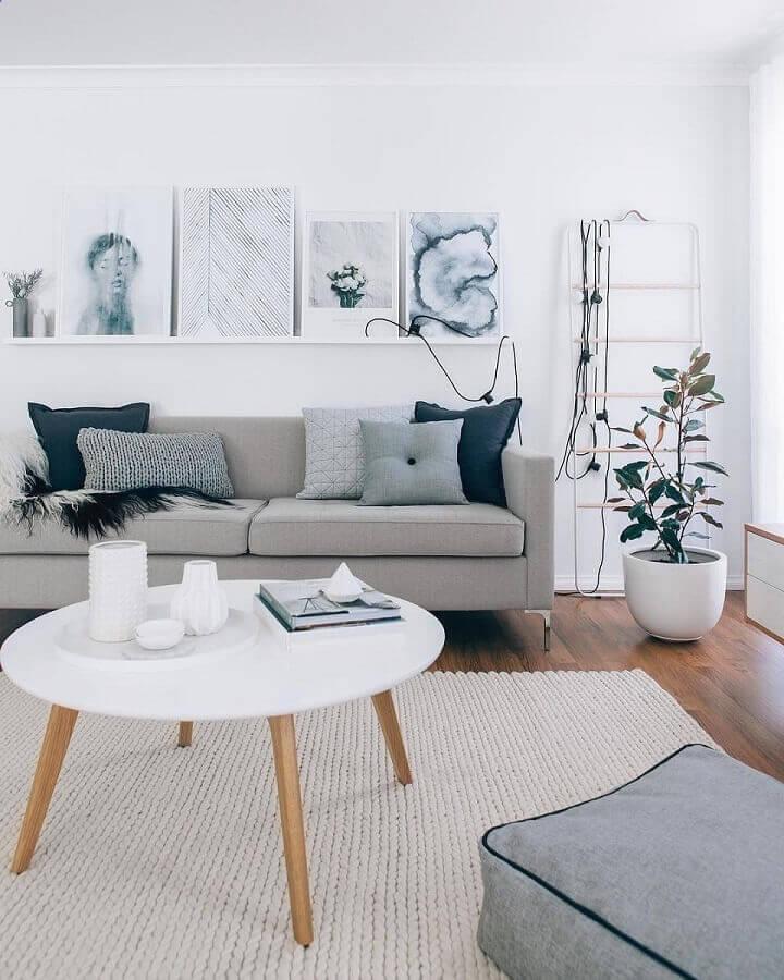 Decoração estilo escandinavo para sala cinza e branco com mesa de centro redonda e prateleiras para quadros Foto Pinterest