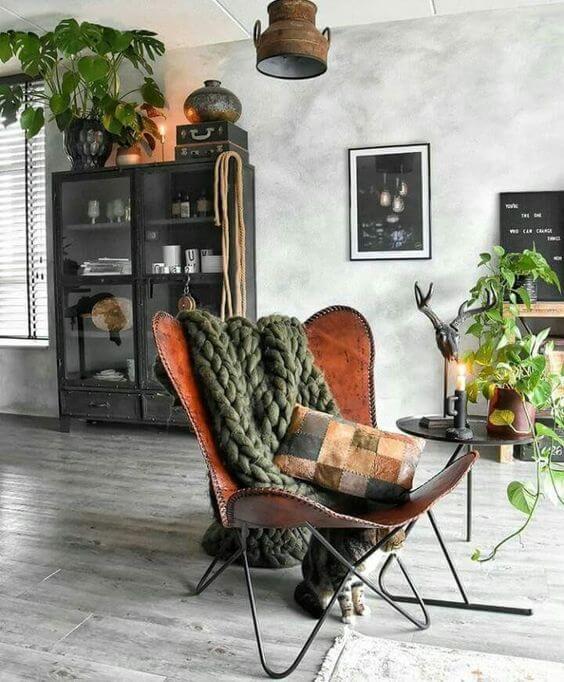 Decoração industrial com poltrona butterfly e manta de trico