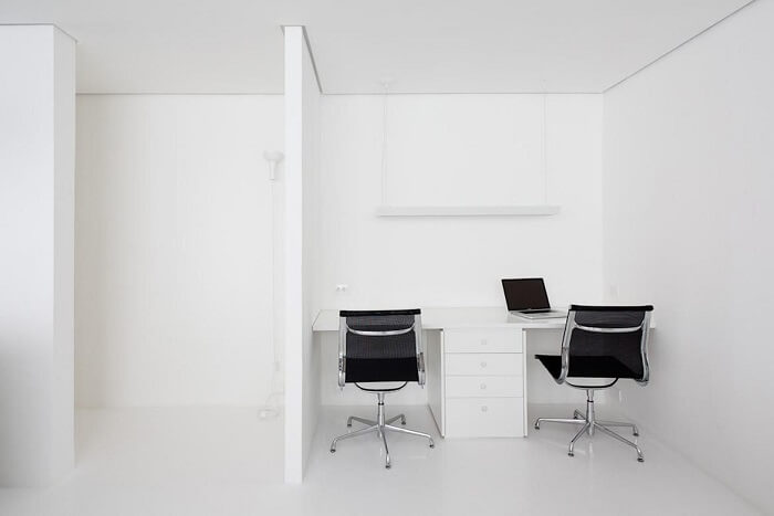 Escritório clean com cadeira preta e escrivaninha com gaveteiro branco. Projeto de Felipe Hess