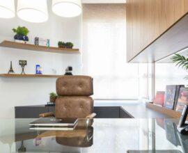 Escritório pequeno planejado com cadeira de couro marrom e bancada de vidro comum. Projeto de Alex Bonilha