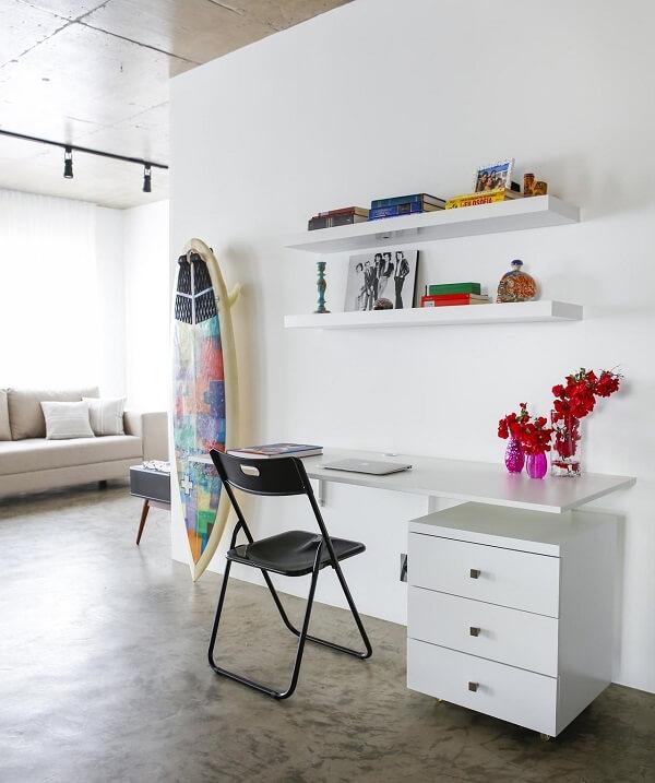 Escrivaninha suspensa e gaveteiro branco decoram o ambiente. Projeto de Buji Decoração Reuso