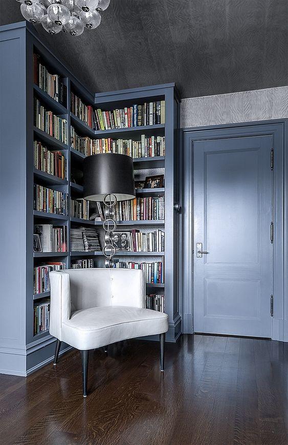 Estante de canto branca com poltrona confortável para cantinho de leitura