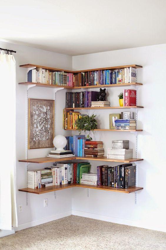 Estante de canto com prateleiras de madeira e livros variados