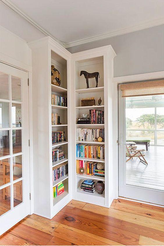Estante de canto para livros na sala de estar com abertura para varanda gourmet