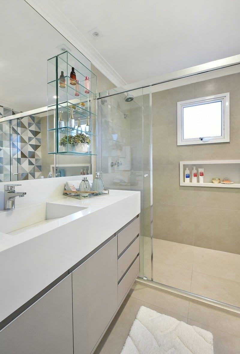 Gabinete cinza, cuba esculpida em mármore prime e prateleiras de vidro decoram o banheiro. Foto: Sidney Doll