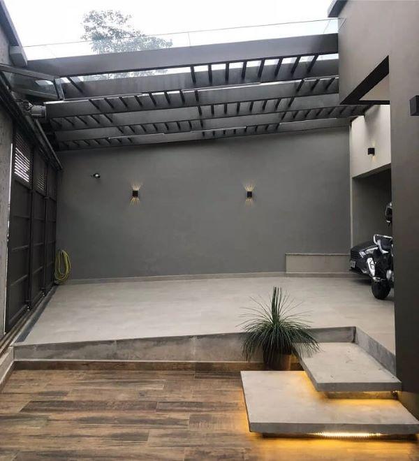 Garagem moderna com cerâmica bege e piso amadeirado na entrada de casa