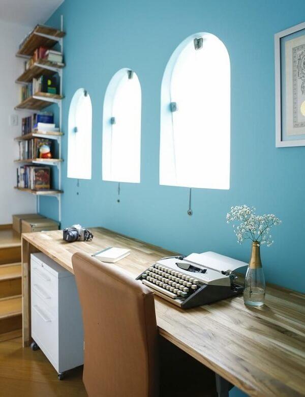 Home office com parede azul, escrivaninha de madeira e gaveteiro branco. Projeto de Buji Decoração Reuso