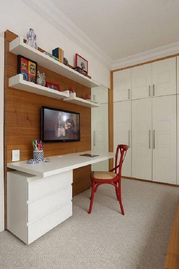 Instalar um gaveteiro branco embaixo do tampo da escrivaninha ajuda a otimizar o espaço. Projeto por Renata Romeiro