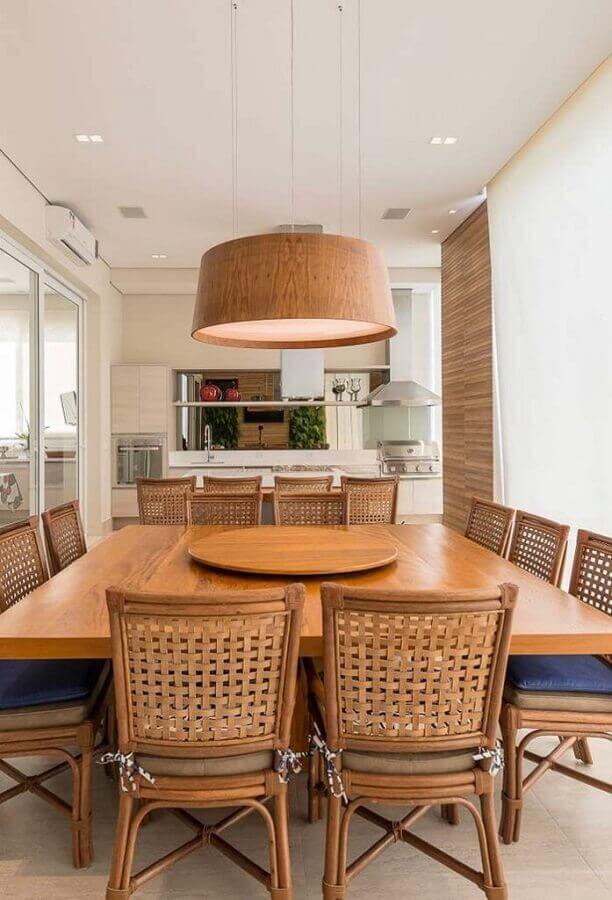 Lustre de madeira para área gourmet decorada com mesa quadrada e churrasqueira de vidro Foto Arkpad