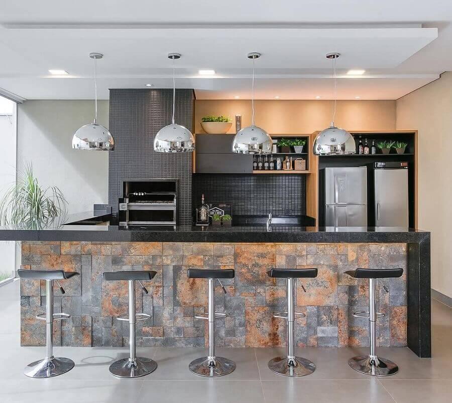 Lustre para área gourmet externa moderna decorada com revestimento preto para churrasqueira Foto Jeito de Casa