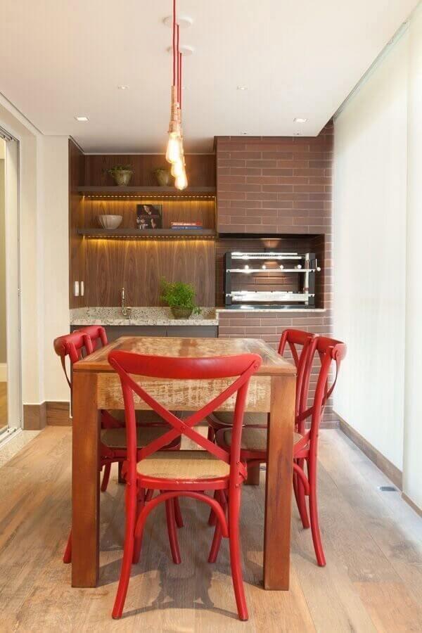 Lustre pendente para área gourmet decorada com cadeiras vermelhas para mesa de madeira rústica Foto Liliana Zenaro