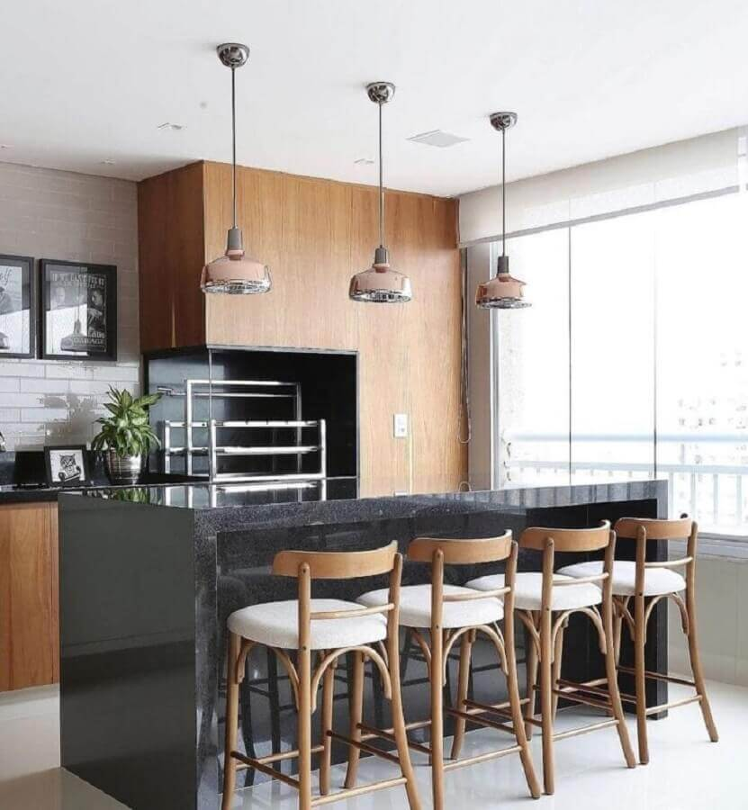 Lustre pendente para área gourmet decorada com revestimento de madeira e bancada de preta Foto Pinterest